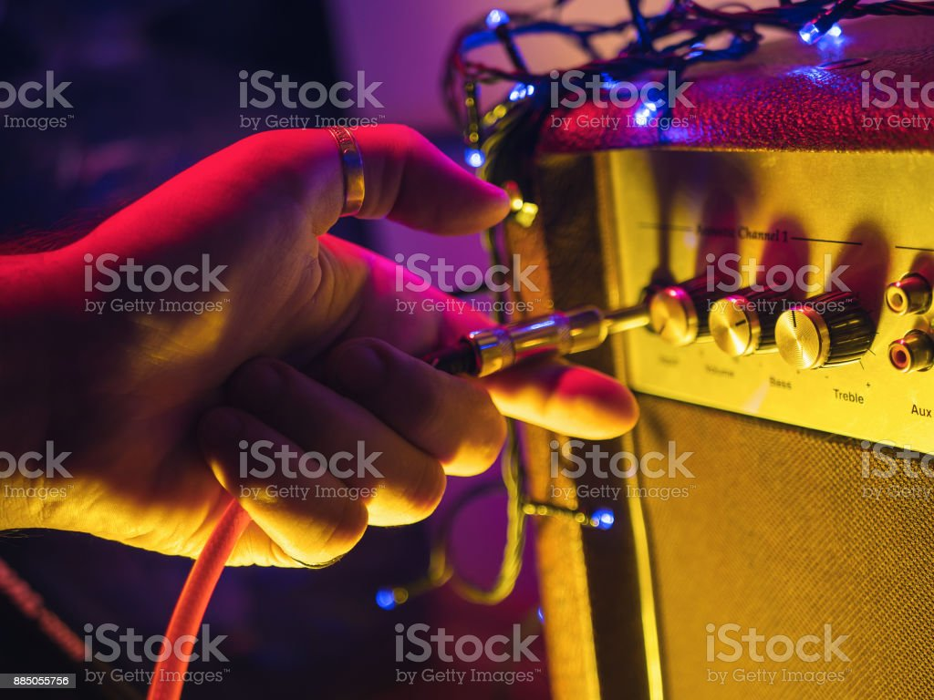 Man plugging jack into the guitar amplifier, closeup, for music, entertainment themes. Neon colorful light stock photo