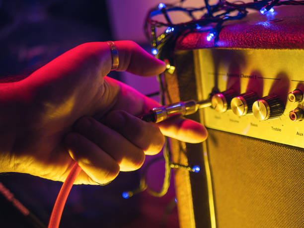 man plugging jack into the guitar amplifier, closeup, for music, entertainment themes. neon colorful light - loudon stock photos and pictures