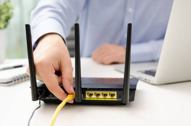 man plugs ethernet cable into router - router foto e immagini stock