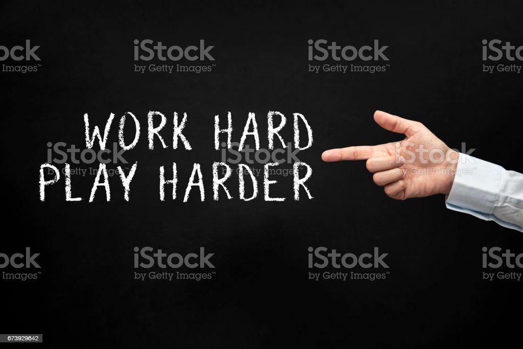 A man poiniting work hard play harder phrase stock photo