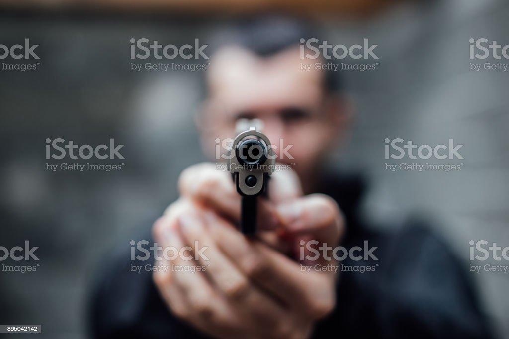 A man pointing a gun at lens stock photo