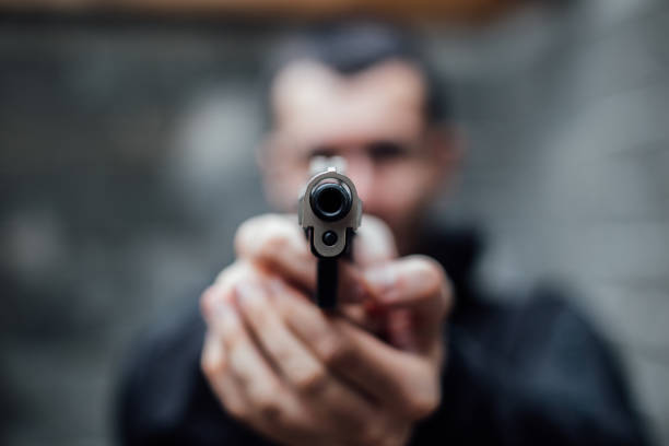 a man pointing a gun at lens - killer stock pictures, royalty-free photos & images