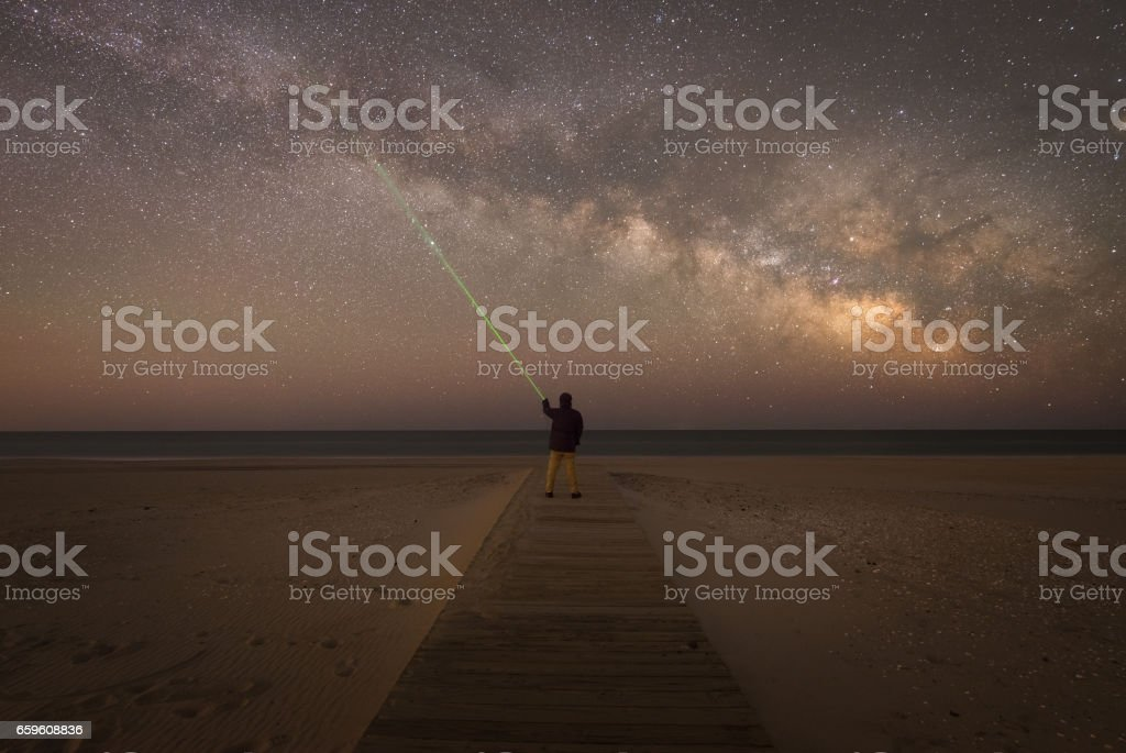 Man pointing a laser at the stars stock photo