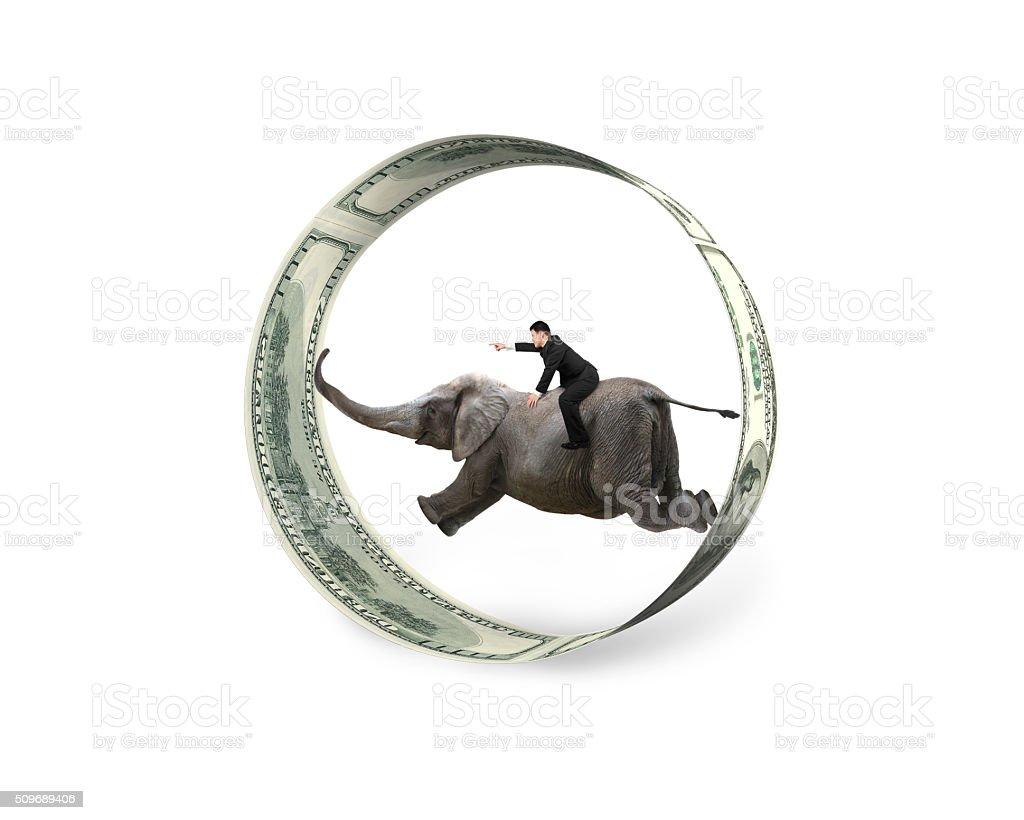 Man pointing finger riding elephant running in dollar bills circ stock photo