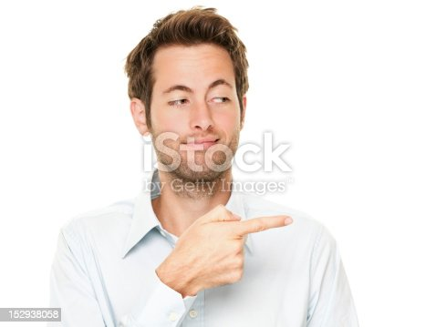 Young man pointing a bit sneaky looking at copy space. Handsome young Caucasian businessman isolated on white background. See more: