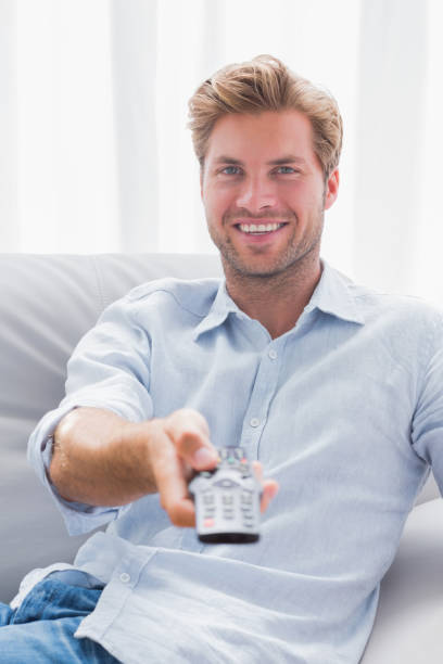Man pointing remote control at the camera stock photo