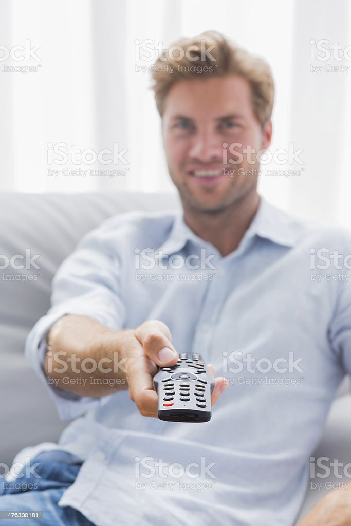 Man pointing remote control toward the camera royalty-free stock photo