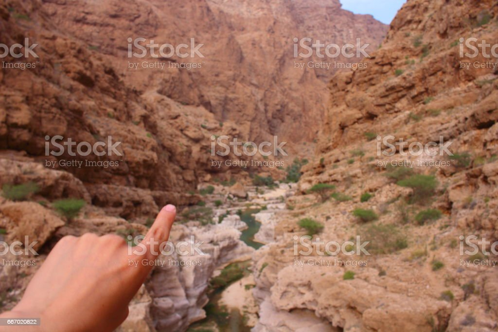 A man pointing to a high canyon in Wadi Shab in Oman stock photo