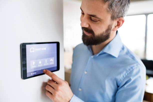 ein mann auf einem tablet mit smart home-bildschirm zu hause zeigen. - tablet mit displayinhalt stock-fotos und bilder