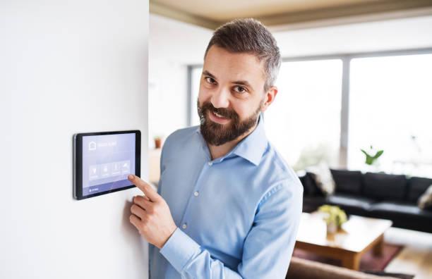 ein mann auf einem tablet mit smart home-bildschirm zeigen. - tablet mit displayinhalt stock-fotos und bilder