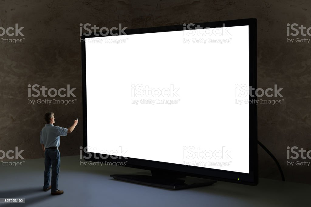 Man pointing tv remote control at world's biggest giant television with blank screen stock photo