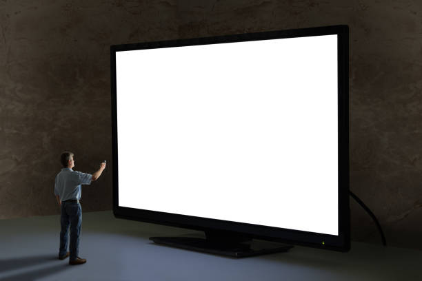 man pointing tv remote control at world's biggest giant television with blank screen - dimly stock pictures, royalty-free photos & images