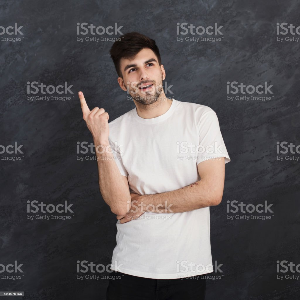 Inspirarion concept. Happy man pointing up, making idea gesture, copy...