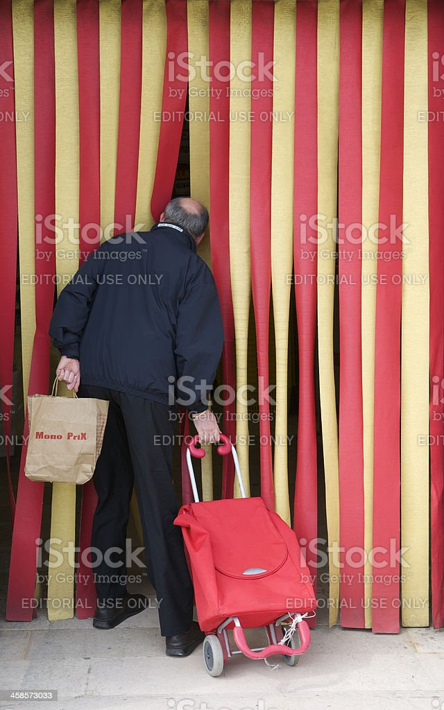 Man Pokes Head through Red and Yellow Strip Door stock photo