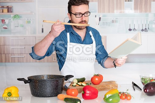 istock Man portrait learning to cook at in the kitchen 1147508417