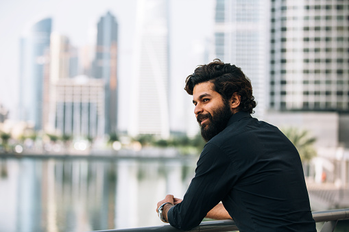 Young man with beard standing outside. He is wearing black shirt and looking at the view and smile
