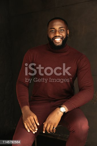 Man portrait. Style. Handsome Afro American guy in wine-colored sweatshirt and pants is looking at camera and smiling, on a dark background