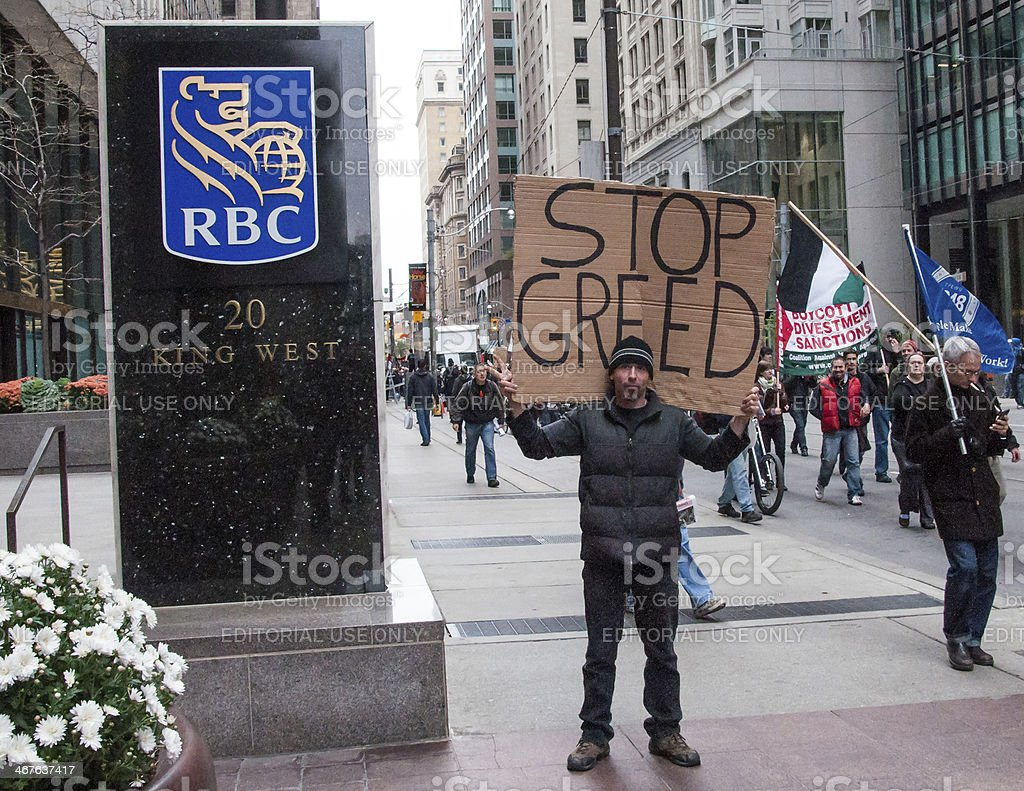 Man Poses in RBC sign asking to stop the greed stock photo