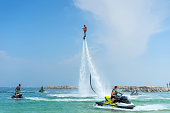 istock Man posing at new flyboard at Caribbean tropical beach. Positive human emotions, feelings, joy. Funny cute men making vacations and enjoying summer. 975730750