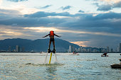 istock Man posing at new flyboard at tropical beach at sunset. 1147682797