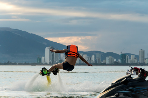 istock Man posing at new flyboard at tropical beach at sunset. 1147682799