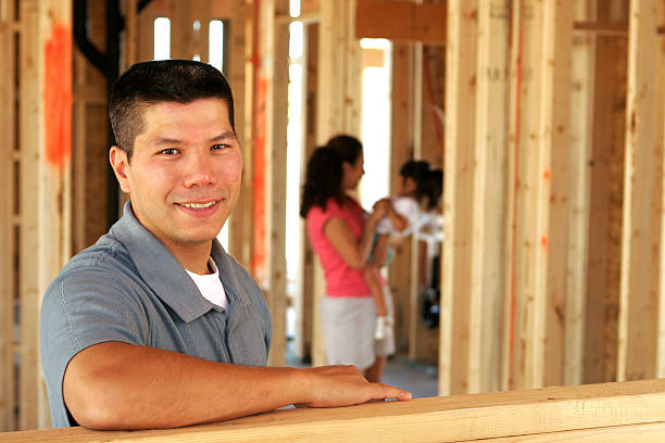 Man posing in a home window still under construction stock photo