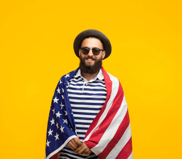 Man posing in American flag Young hipster man in sunglasses smiling at camera while posing wrapped in American flag on orange background. american flag tattoos for men stock pictures, royalty-free photos & images