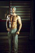 Stylish urban man posing in gym wearing a cap
