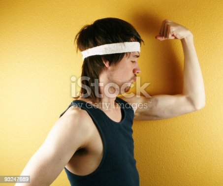 istock Man posing in retro workout clothes flexing muscle 93247689