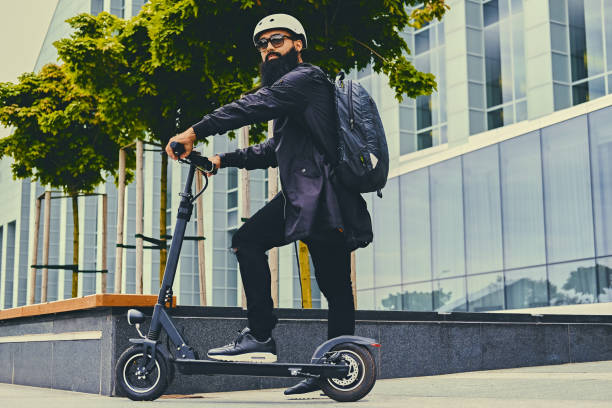 a man posing on electric scooter. - electric push scooter stock photos and pictures