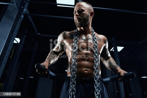 From below view of athletic young man with perfect muscular shirtless body doing triceps dips on parallel bars in gym. Tattooed bearded male posing with chains on neck in dark atmosphere.