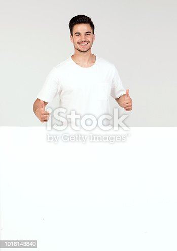 istock Man posing with white empty board. 1016143840