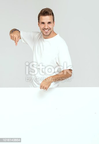 istock Man posing with white empty board. 1016143854