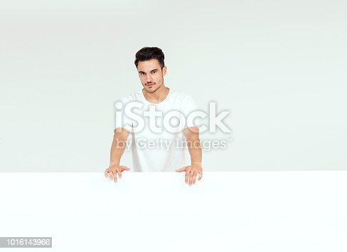 istock Man posing with white empty board. 1016143966