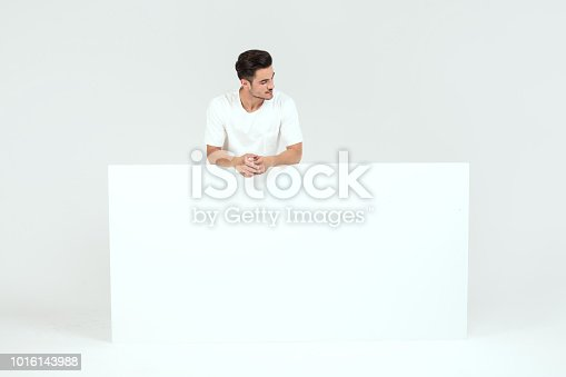 istock Man posing with white empty board. 1016143988