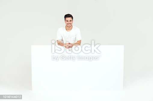 875677322istockphoto Man posing with white empty board. 1016144012