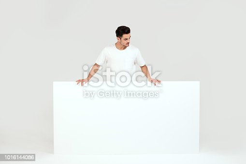 istock Man posing with white empty board. 1016144086