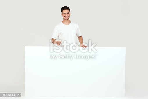 istock Man posing with white empty board. 1016144122