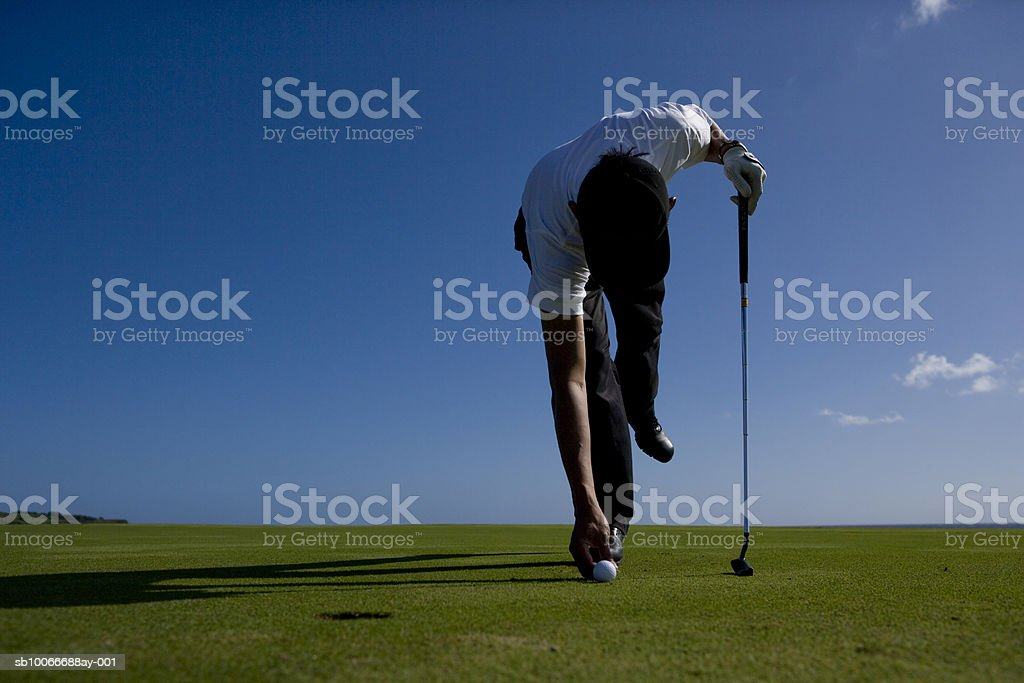 Man positioning golf ball on golf course 免版稅 stock photo