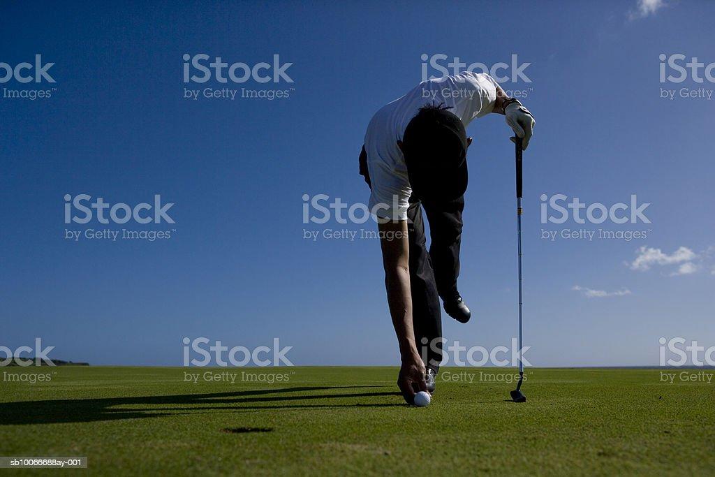 Uomo posizionamento Pallina da golf sul campo da golf foto stock royalty-free