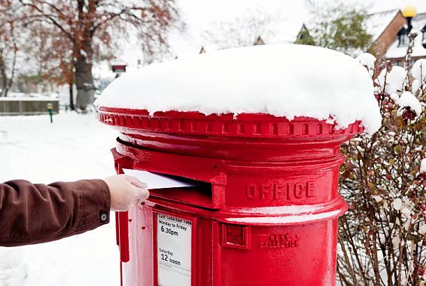 mann posting buchstabe in schneebedeckte british postfach - beckenham town stock-fotos und bilder