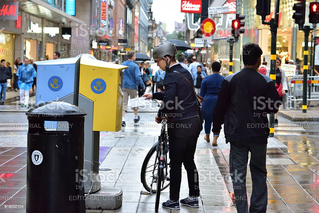 Man posting mail in mailbox Postnord. With bike stock photo