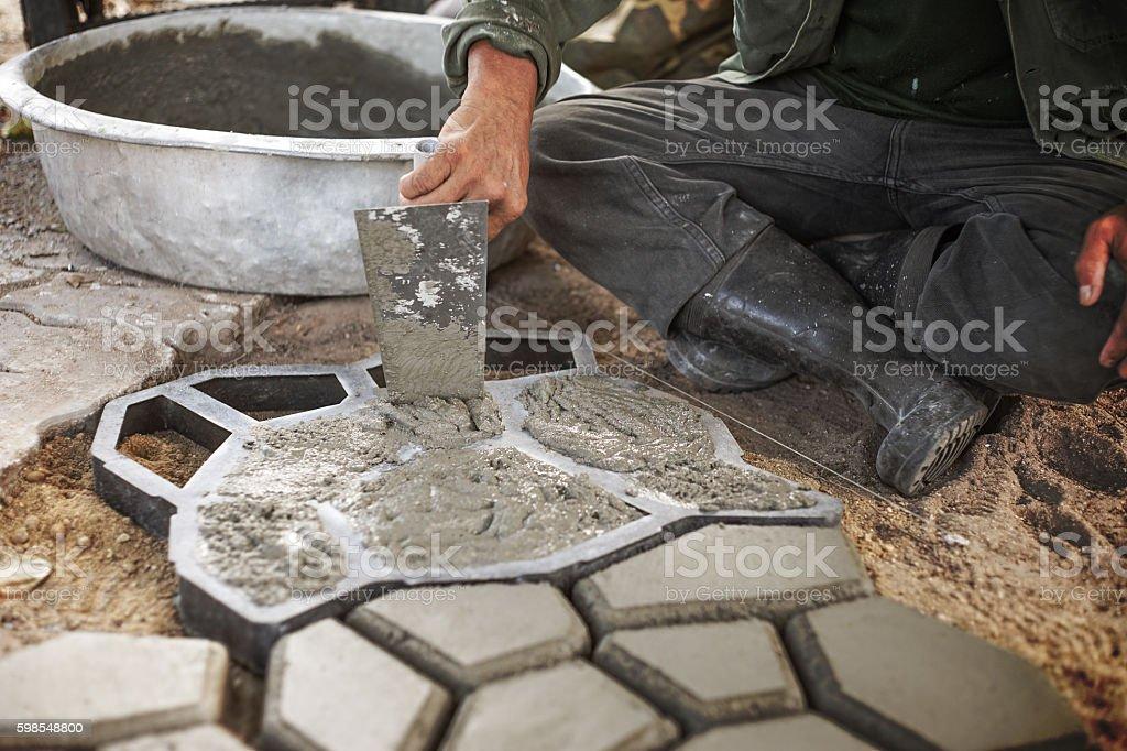 Man pour cement to a Mold to Make Concrete Pavers photo libre de droits