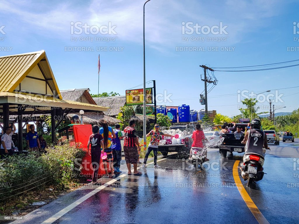 Man pour water on motorbike driver celebrate traditional Thai New Year - Songkran Festival royalty-free stock photo