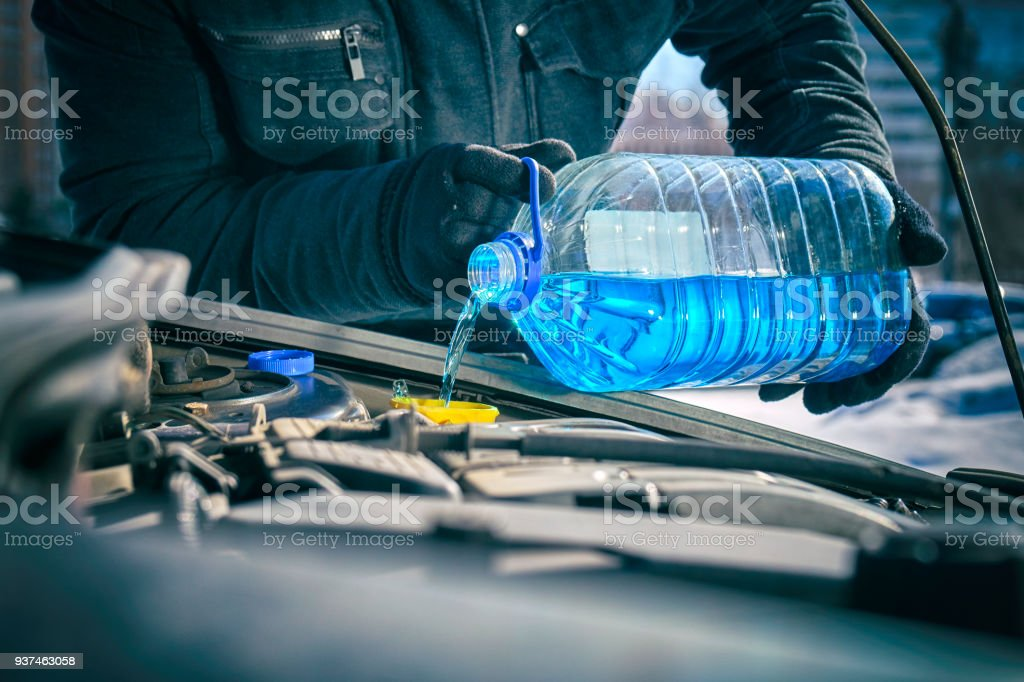 Man pouring an antifreeze liquid in a windshield washer tank of a car stock photo