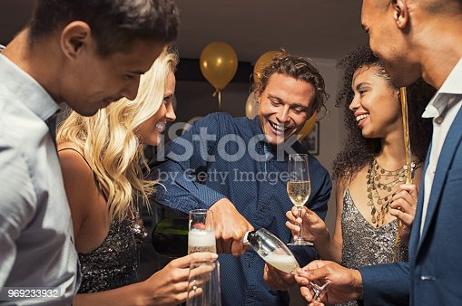 istock Man pouring champagne in flutes 969233932