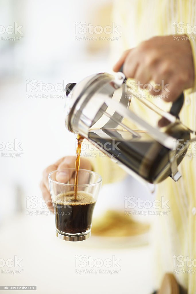 Man pouring coffee from cafetiere in to mug, close-up, mid section royalty-free stock photo