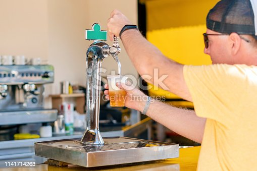 istock Man pouring fresh beer in self service bar - with all inclusive badge 1141714263