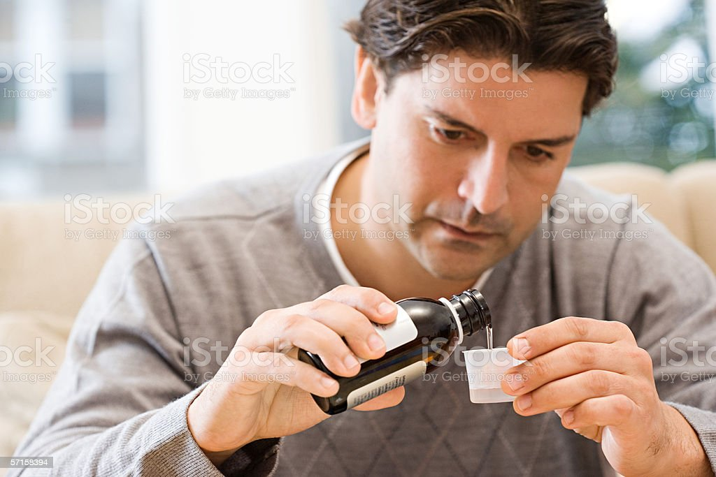 Hombre Verter medicamento - foto de stock