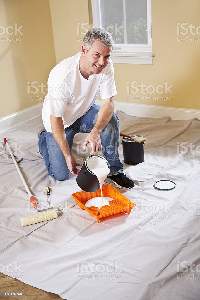 Man pouring paint into tray royalty-free stock photo